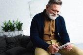 Fotografie smiling bearded senior man in eyeglasses using digital tablet at home
