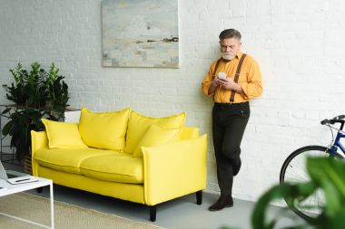 stylish bearded senior man using smartphone at home