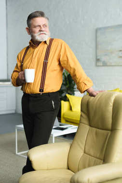 senior man holding cup of coffee and looking away while standing near armchair at home