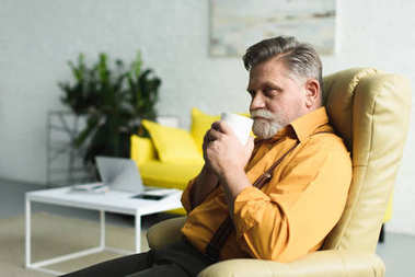 smiling bearded senior man drinking coffee from cup while sitting on armchair at home