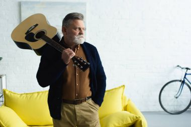 confident senior man holding guitar and looking away at home