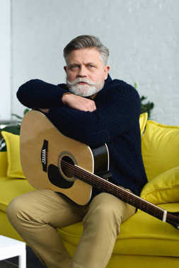handsome bearded senior man sitting with guitar and looking at camera