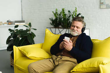 smiling bearded senior man in headphones sitting on sofa and listening music with smartphone
