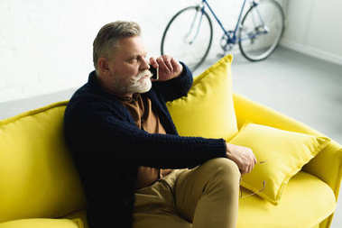 bearded senior man talking by smartphone and looking away while sitting on sofa at home