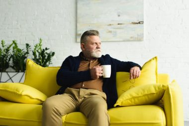 pensive senior man holding cup of coffee and sitting on yellow couch at home