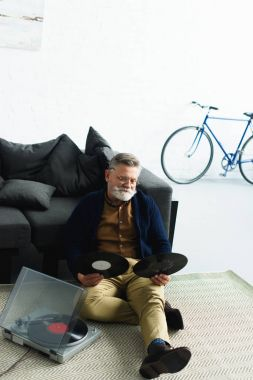 high angle view of bearded senior man in eyeglasses holding vinyl records while sitting on carpet at home