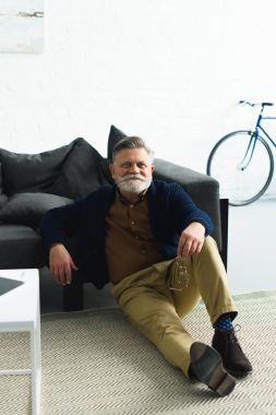 handsome smiling senior man holding eyeglasses and sitting on carpet at home