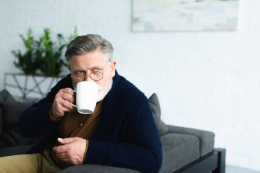 bearded senior man in eyeglasses drinking from cup and looking away at home