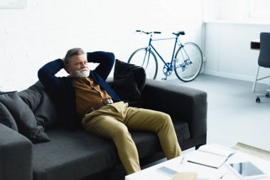 handsome bearded senior man sitting with hands behind head on sofa at home