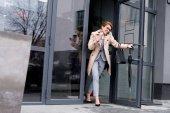 Fotografie lächelnde Geschäftsfrau sprechen auf Smartphone beim verlassen Businesscenter