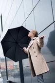 Fotografie podnikatelka v stylovém kabátě s deštníkem na ulici