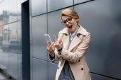 Fotografie Porträt der Geschäftsfrau mit Smartphone zeigt Mittelfinger auf Straße