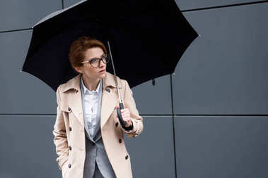 portrait of businesswoman in stylish coat with umbrella on street
