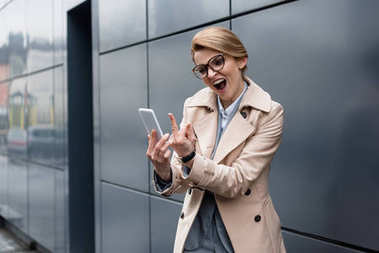 portrait of businesswoman with smartphone showing middle finger on street