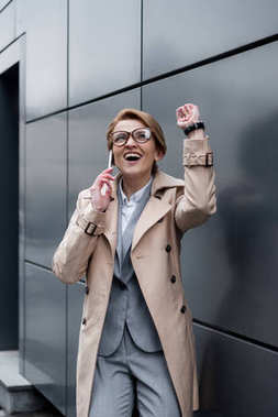 excited gesturing businesswoman talking on smartphone on street