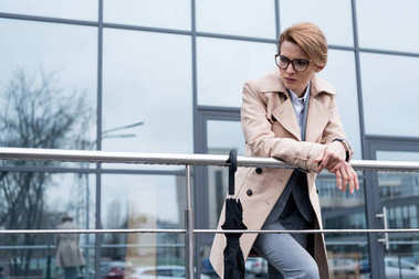 portrait of thoughtful businesswoman in coat standing on street