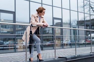 businesswoman in stylish coat standing on street