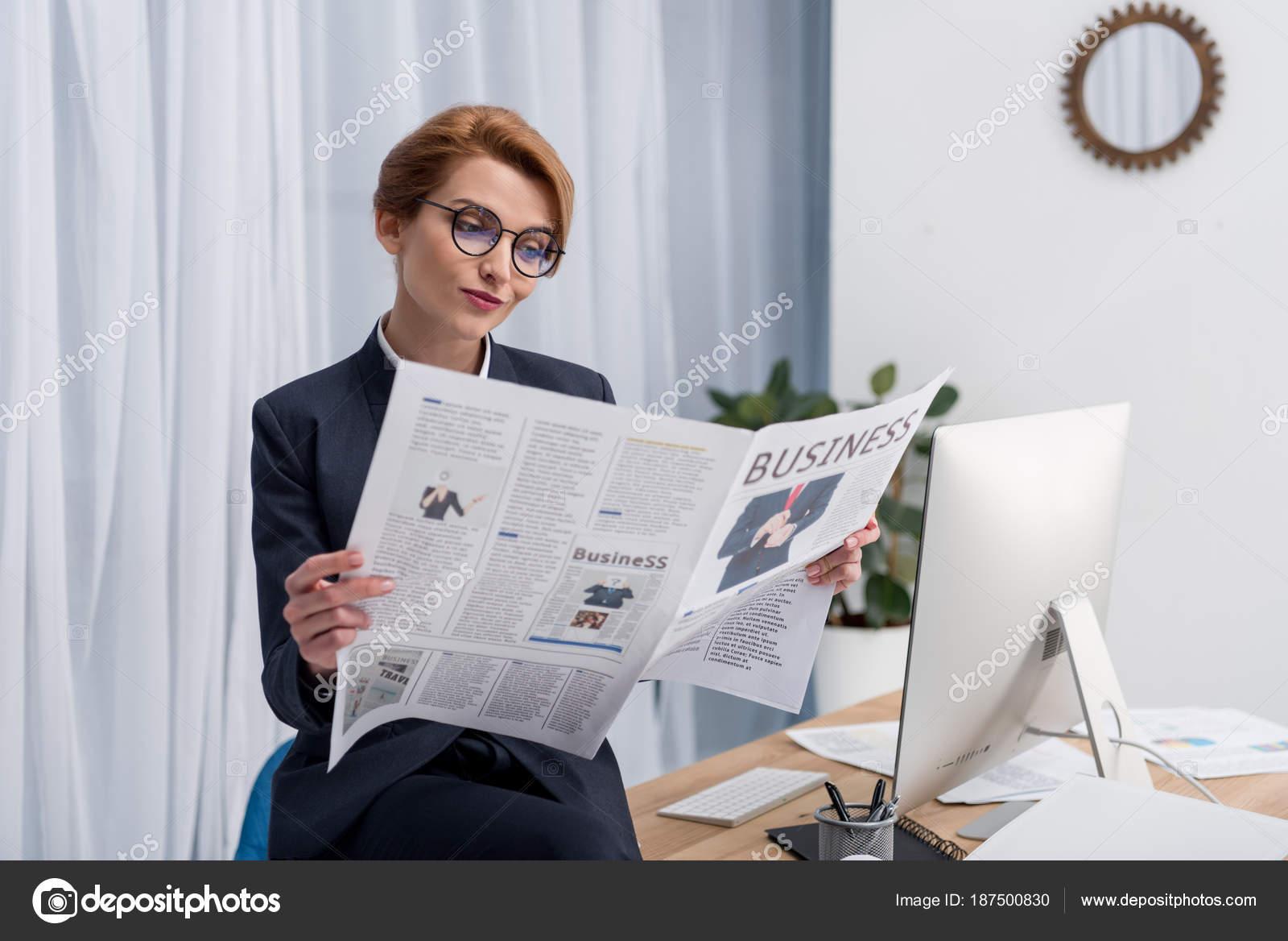 Homme d affaires souriant avec journal assis au bureau