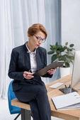 Koncentrovaná podnikatelka s Poznámkový blok na pracovišti v úřadu