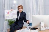 Fotografie verwirrt Geschäftsfrau mit Dokument und Smartphone am Arbeitsplatz im Büro
