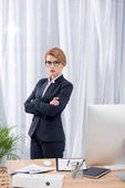 Fotografie portrait of businesswoman in suit with arms crossed standing in office
