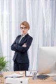 portrét podnikatelka v obleku s rukama zkříženýma stojící v úřadu