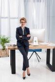 Fotografie lächelnde Geschäftsfrau mit Armen gekreuzt stützte sich auf Tisch im Büro