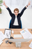 Fotografia vista dallalto della donna di affari che mostra il segno di pace al posto di lavoro in ufficio
