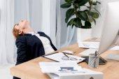 unavený podnikatelka v obleku na pracovišti s dokumenty v kanceláři