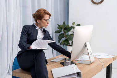 concentrated businesswoman with notepad at workplace in office