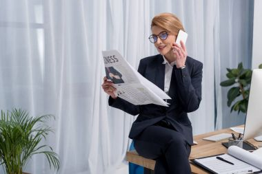 smiling businesswoman reading newspaper and talking on smartphone at workplace in office