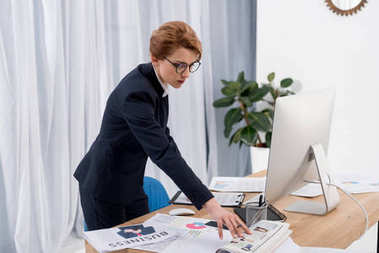 concentrated businesswoman doing paperwork at workplace in office