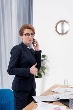businesswoman winking at camera and showing thumb up while talking on smartphone at workplace in office