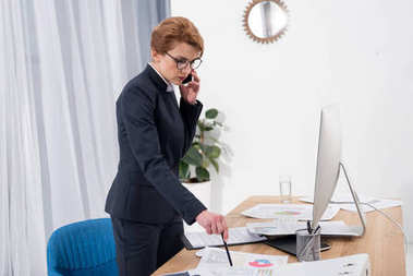 side view of businesswoman talking on smartphone at workplace in office