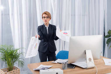 Confused businesswoman with documents at workplace in office stock vector