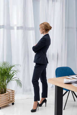 side view of pensive businesswoman in suit looking out window in office