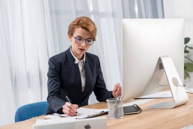 focused businesswoman working at workplace with documents computer screen in office