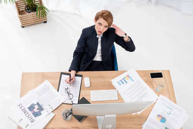 overhead view of overworked businesswoman at workplace in office