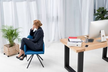 pensive businesswoman in suit sitting on chair in office