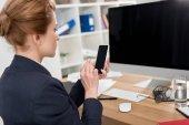 Seitenansicht der Geschäftsfrau im Anzug mit Smartphone am Arbeitsplatz im Büro
