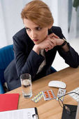 Fotografie nachdenklich Geschäftsfrau im Anzug am Arbeitsplatz mit Pillen und Glas Wasser im Büro sitzen