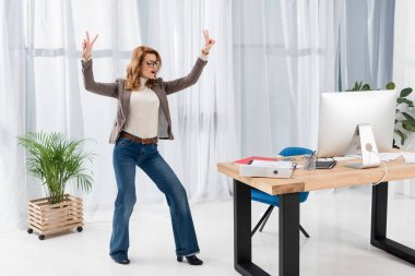 stylish businesswoman showing peace sign in office
