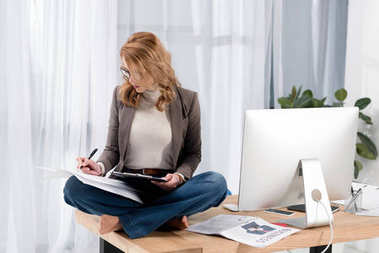 businesswoman in eyeglasses doing paperwork while sitting on table in office