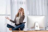 Fotografie glücklich Geschäftsfrau mit Papieren am Smartphone beim Sitzen am Tisch im Büro sprechen