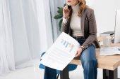 Fotografie oříznutý snímek podnikatelka s doklady rozhovor na smartphone a zároveň sedí na stole v kanceláři