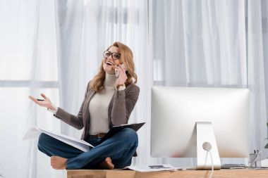 happy businesswoman with papers talking on smartphone while sitting on table in office