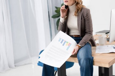cropped shot of businesswoman with papers talking on smartphone while sitting on table in office