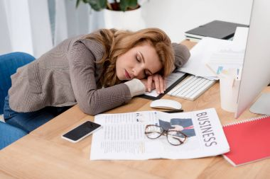 exhausted businesswoman sleeping at workplace with documents in office