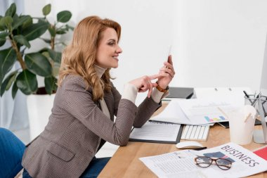 side view of smiling businesswoman using smartphone at workplace with documents in office