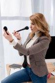 Fotografie stilvolle Geschäftsfrau Blick auf Spiegel beim Schminken am Arbeitsplatz im Büro